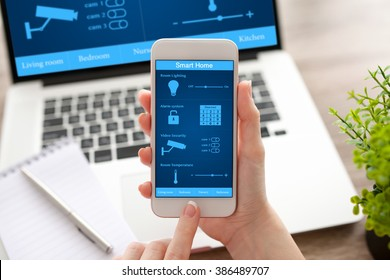 woman hands holding white phone and notebook with app smart home on the screen