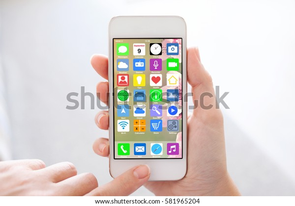 woman hands holding white touch phone with home screen icons apps