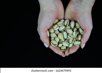 Woman hands holding a wooden bowl with mixed nuts. Healthy food and snack. Walnut, pistachios, almonds, hazelnuts and cashews