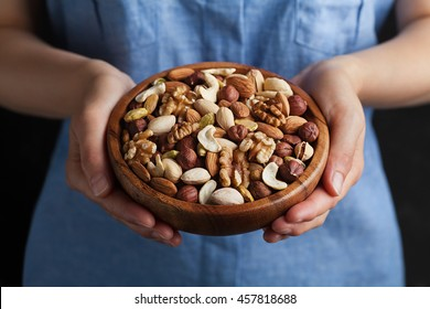 Woman hands holding a wooden bowl with mixed nuts. Healthy food and snack. Walnut, pistachios, almonds, hazelnuts and cashews.