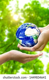 Woman hands holding world or globe give to another hand on earth day.Environment conservation and energy saving concept.Elements of this image are furnished by NASA.