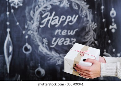 Woman hands holding wrapped gift box on Happy New Year background