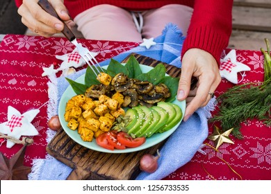 Woman hands holds buddha bowl for Christmas lunch, dinner. Eat fried tofu, avocado slices, mushrooms, tomatoes, spinach. Take healthy vegetarian food. Red tablecloth.