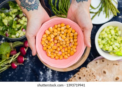 Woman hands holds cooked chickpea beans in a bowl. Vegan food. Vegetarian food.