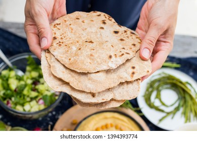 Woman hands holds hot homemade baked whole wheat flour Indian chapati crispy flat breads, pita, roti or paratha. Vegan food, vegetarian healthy food.