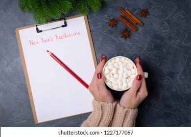 Woman hands holds mug with cacao, ready to write new year's resolutions on blank list on dark background. Flat lay. Top view. New year concept. Target success concept. Personal goals.