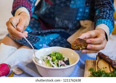Woman hands holds okroshka - a cold soup made from cucumber, kvass, radish, dill, parsley. Vegan raw okroshka with coconut milk yoghurt, lemon, garlic. Vegetarian lunch or dinner. Healthy food.