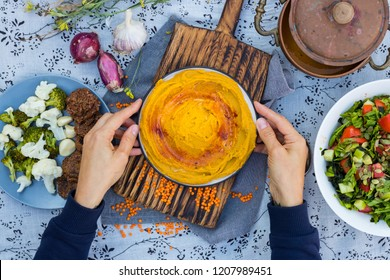 Woman hands holds and takes yellow chickpea hummus. Traditional Israeli Arabian Middle East homemade hummus food with tahini, olive oil and paprika. vegan lunch, vegetarian dinner, healthy food
