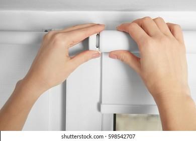 Woman hands installing window blinds, closeup