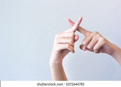 Woman hands isolated showing  crossing fingers forming an x on grey background, gesture of wrong.