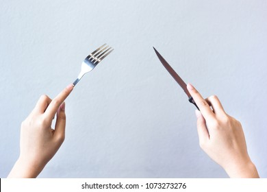 Woman hands isolated showing two hands holding knife and fork on grey background, gesture of eating dinning.