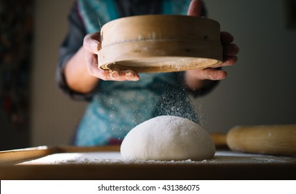 Woman hands knead dough for pasta, ravioli or dumplings. Step by step guide. Closeup, flour flies in air