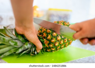 Woman hands with knife cutting pineapple top on cutting board in domestic kitchen. Close-up.