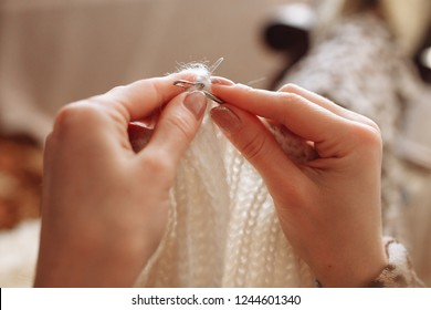 The woman hands knit natural woolen clothes. Knitting needles close-up. Horizontal photo. Freelance creative working. Handcraft concept
