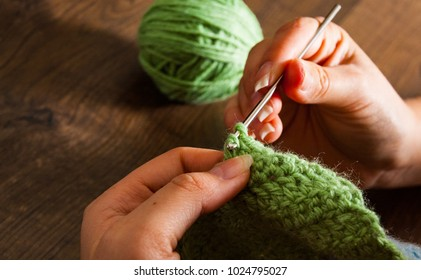 woman hands knitting with crochet hook on a wooden background
