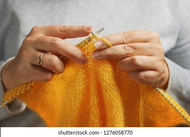 Woman hands knitting with knitting needles and yellow soft wool yarn. Needlework concept.