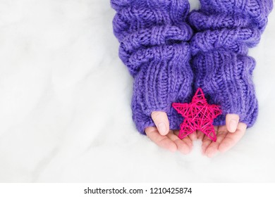Woman hands in light teal knitted mittens are holding star on snow background. Winter and Christmas concept.