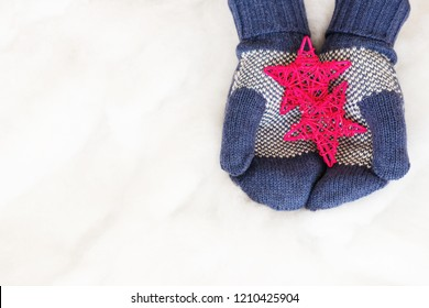 Woman hands in light teal knitted mittens are holding stars on snow background. Winter and Christmas concept.