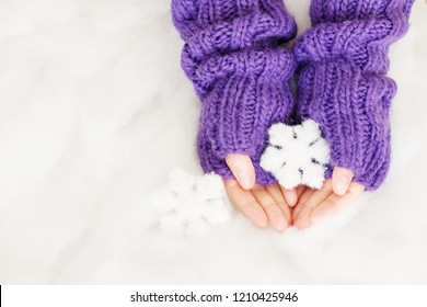 Woman hands in light teal knitted mittens are holding snowflakes on snow background. Winter and Christmas concept.