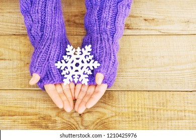 Woman hands in light teal knitted mittens are holding snowflake on wooden background. Winter and Christmas concept.
