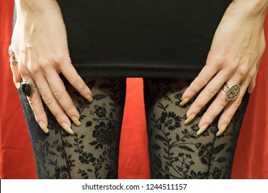 Woman hands with long nails on the black miniskirt wearing tights