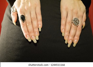 Woman hands with long nails on the black miniskirt close up