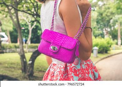 Woman hands with luxury handmade snakeskin leather handbag. Python snake fashionable handbag. Outdoors, Bali island.