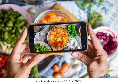 Woman hands make smartphone food photography of corn, potato, pepper vegetables hot soup. Trendy phone food photo for social media or blogging. Vegan lunch, vegetarian dinner, healthy diet. Top view