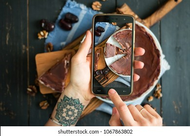 Woman hands make smartphone photo of raw vegan dessert. Chocolate sweet tart with dates (cake or pie). Phone photography of lunch or dinner for social networks. Top view.Vegetarian healthy food
