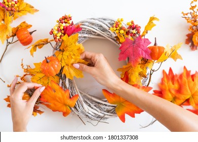 Woman hands makes an autumn wreath at the door from yellow leaves, decorative pumpkins and berries on a white background. Top View