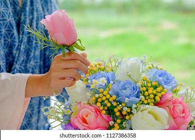 Woman hands making flower composition at florist workshop. Do it yourself concept.