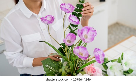 Woman hands making flower composition at florist workshop. Do it yourself concept.