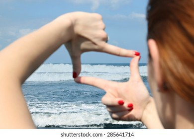 Woman hands making a frame against the blue ocean blur