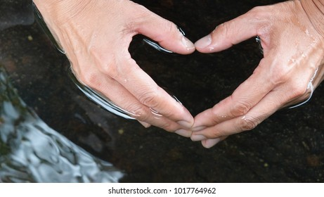 Woman hands making heart shape in clean and clear water. Abstract background.