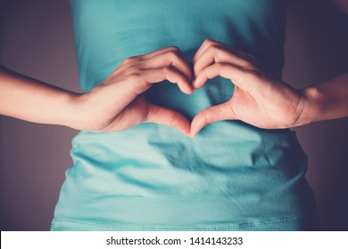 Woman hands making a heart shape on her stomach, healthy bowel degestion, probiotics and prebotics  for gut health