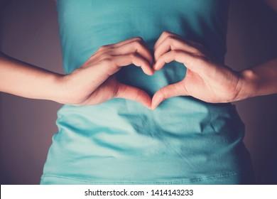 Frauen, die eine Herzform auf ihrem Magen machen, Darmdegestion, Probiotika und Präbotika für die Darmgesundheit