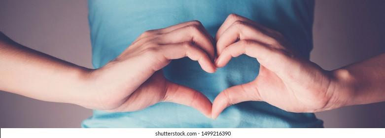 Woman hands making a heart shape on her stomach, healthy bowel degestion, probiotics  for gut health, leaky gut, woman health