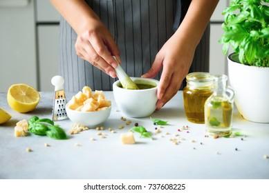 Woman hands making italian pesto in bowl. Ingredients - basil, lemon, parmesan, pine nuts, garlic, olive oil and salt on rustic wooden background. Top view, flat lay, copyspace