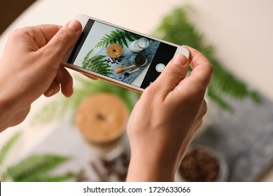 Woman hands making picture by phone for social media  trendy fluffy Korean drink with whipped cream dalgona coffee with almond milk on marble board.