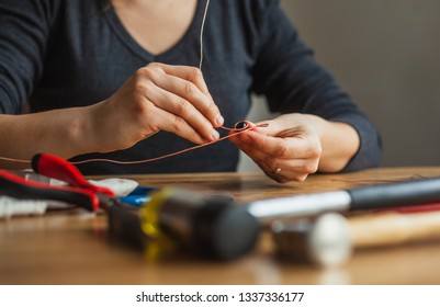 woman hands making wire wrapped jewelry preparation process dark close up top view. Female girl bends  crafts handmade copper  wire working tools on the table. Handmade bijouterie jewellery adornment.
