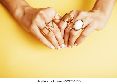 woman hands with manicure and jewelry ring on yellow background, beauty style concept