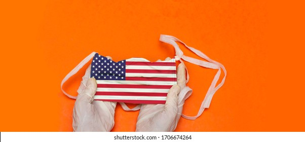 woman hands with medical gloves holding Medical mask with USA flag. pandemic concept in USA. attribute of coronavirus outbreak