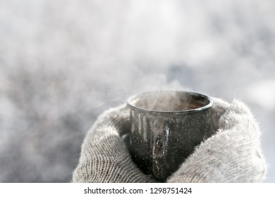 Woman hands in mittens holding a cozy steaming mug or cup with hot cocoa, tea or coffee. Beautiful girl enjoying winter morning or evening outdoors under snowfall. Winter and Christmas time concept
