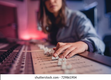 Woman hands mixing audio in recording studio. Female hands working on music mixer. Music production technology.