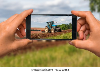 Woman hands with mobile cell phone to take a photo of tractor at work on a field