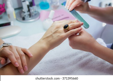 Woman hands in a nail salon receiving a manicure by a beautician with nail file, nail filing. Woman getting nail manicure, body care, spa treatments. Close up, shallow dof.