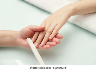 Woman hands in a nail salon receiving a manicure.  Nail filing. Close up, selective focus.