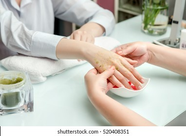 Woman hands in a nail salon receiving a  hand scrub peeling by a beautician. SPA manicure, hand massage  and body care, spa treatments.