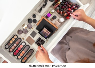 Woman hands neatly organizing makeup or cosmetics in the drawer of vanity dressing table and leaving her jewellery on dressing table surface. Visagiste is taking out vanity case of cosmetic powders