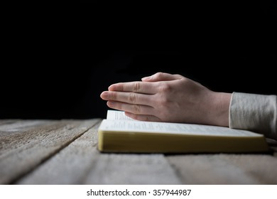 woman hands on bible. she is reading and praying over bible over wooden table